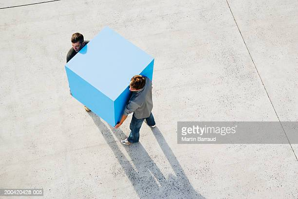 Two men carrying large blue block, elevated view