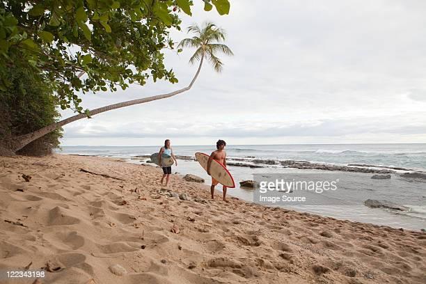 dos hombres, con tablas de surf en la playa - paisajes de puerto rico fotografías e imágenes de stock