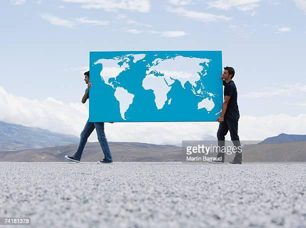 Due uomo portare la mappa del mondo all'aperto