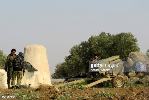 Two men chat as an other man prepares a multibarrel rocket launcher within the clashes between armed opposition group Tahrir alSham and Assad Regime...
