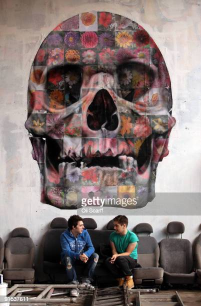 Two men chat under a floral skull artwork by 'Part2ism' in the 'One Foot in the Grove' exhibition of street art by 'Mutate Britain' under the Westway...