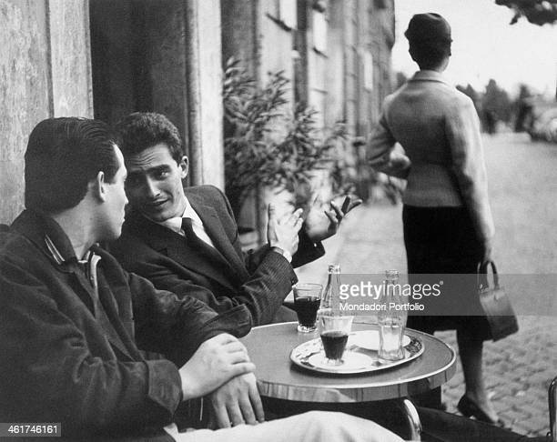Two men chatting at the outdoor table of a café in front of two bottles of CocaCola A woman looking back 1959