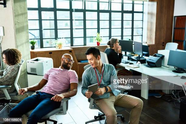 two men chatting in office with digital tablet - gossip stock pictures, royalty-free photos & images