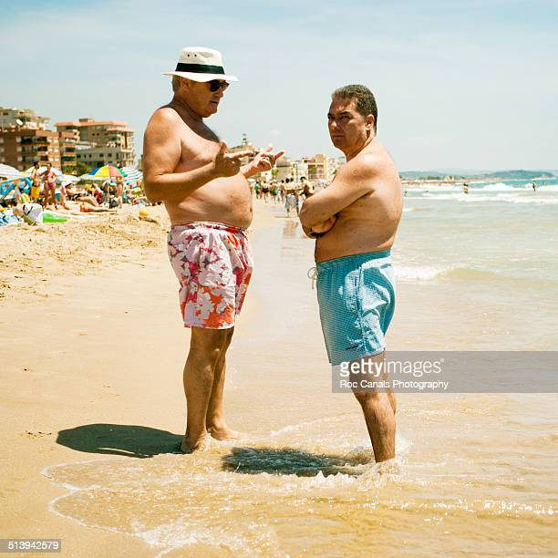 Two men chatting on the beach