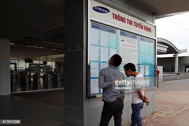 Two men check an employment information board at the Samsung Electronics Vietnam Co Plant after finishing their shift at Yen Phong Industrial Park in...