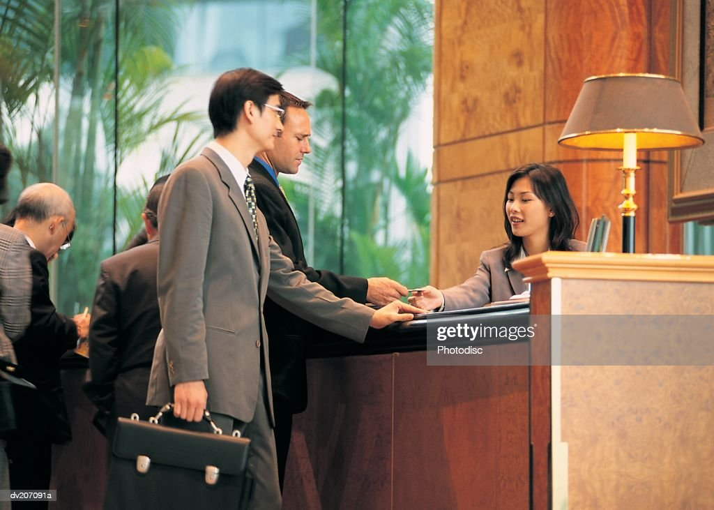 Two men checking into hotel : Stock Photo