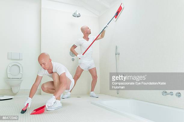 Two men cleaning bathroom