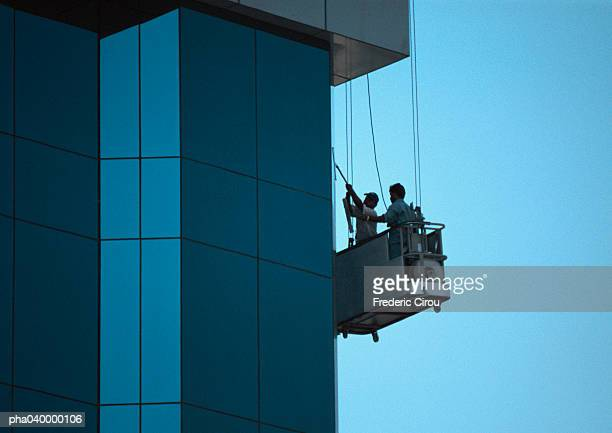 two men cleaning skyscraper's facade - window cleaning stock photos and pictures