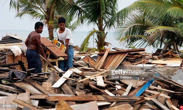 Two men clear debris after the massive tsunami wave swept across coastal Sri Lanka December 28 2004 in Colombo Sri Lanka Over 55000 people have been...