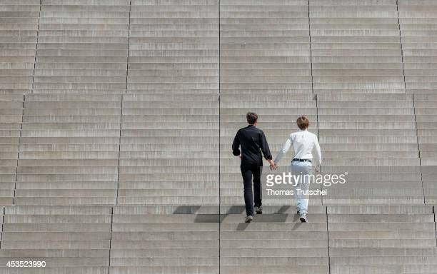Two men climb up stairs close to each other hand in hand on August 12 2014 in Berlin Germany