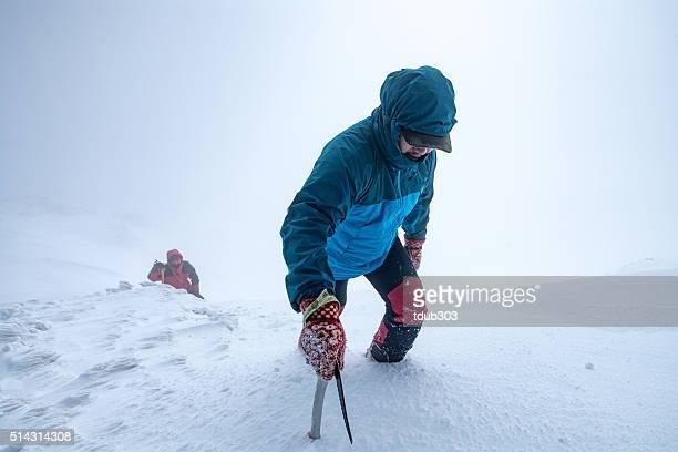 Zwei Männer Klettern einen Gipfel der Berge in den Wolken