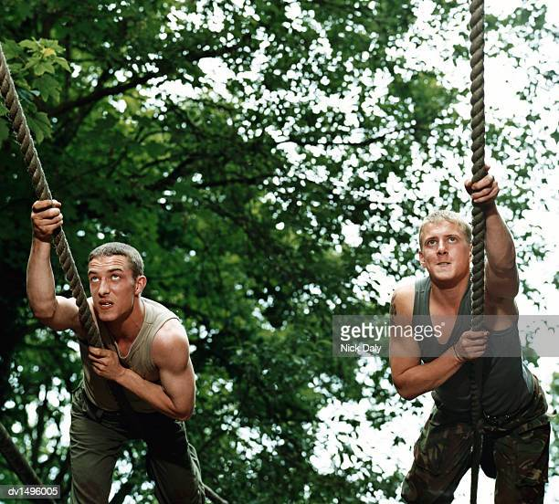 Two Men Climbing Ropes on an Assault Course