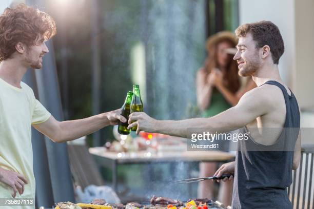 Two men clinking beer bottles at barbecue grill