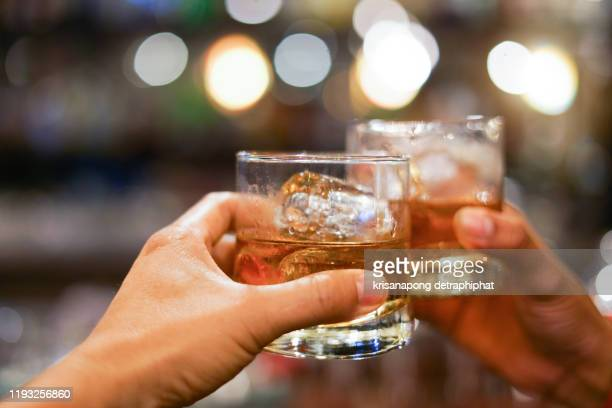 two men clinking glasses of whiskey drink alcohol beverage together at counter in the pub - bibita foto e immagini stock