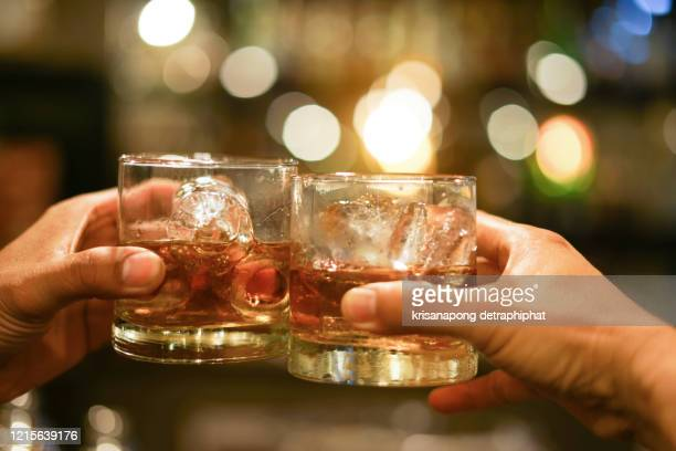 two men clinking glasses of whiskey drink alcohol beverage together at counter in the pub - bourbon whisky foto e immagini stock