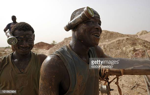 RETRAITE** Two men come out of a hole where they where digging for gold in Namisgmathe largest gold washing site in the country some 200 kilometers...