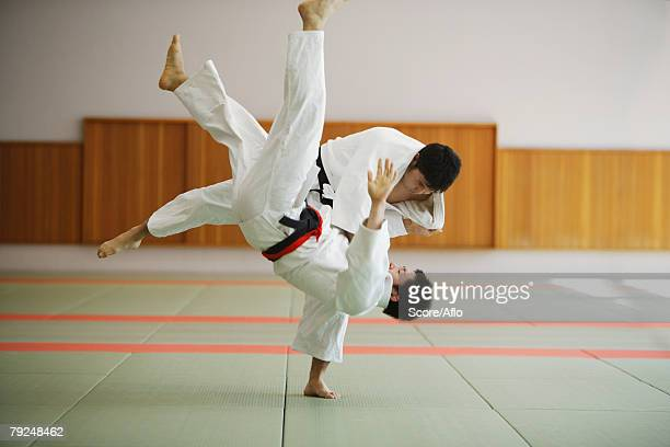 two men competing in a judo match - judo stock photos and pictures