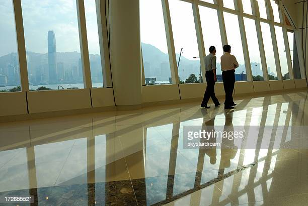 Two men conversing in empty hallway with tall windows