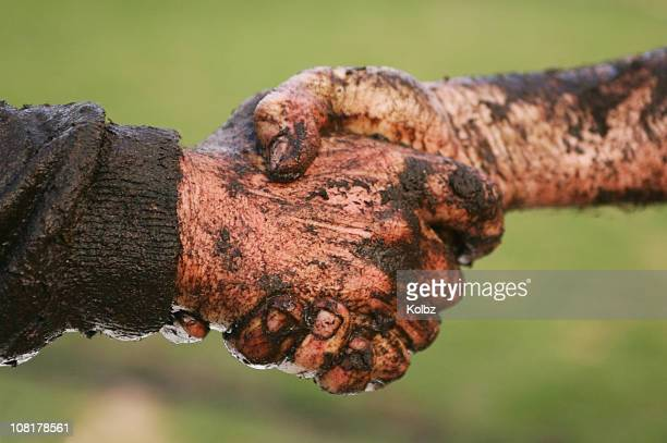 Two Men Covered in Mud Shaking Hands