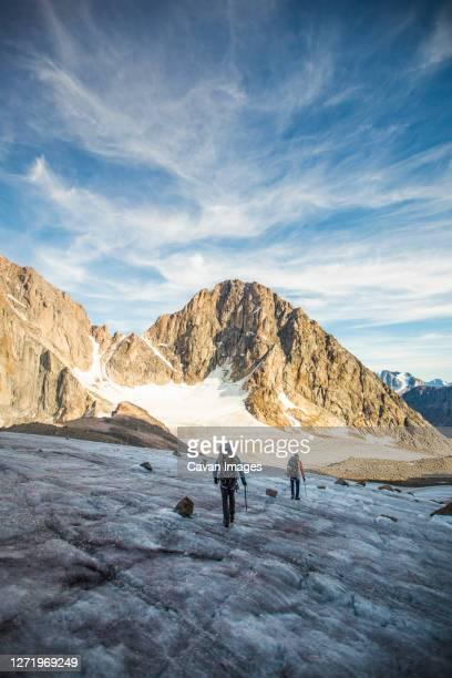 two men cross a glacier through a high mountain pass. - バフィン島 ストックフォトと画像