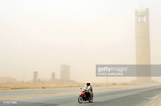 Two men cross a main road on a motorbike through a sandstorm over the Saudi capital Riyadh on March 18 2012 Saudi meteorological authorities have...