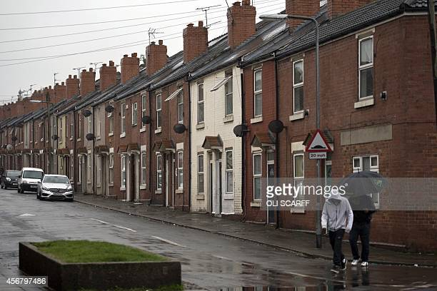 Two men cross a street in Rotherham South Yorkshire North England on October 6 2014 An inquiry revealed on August 26 2014 that some 1400 minors were...