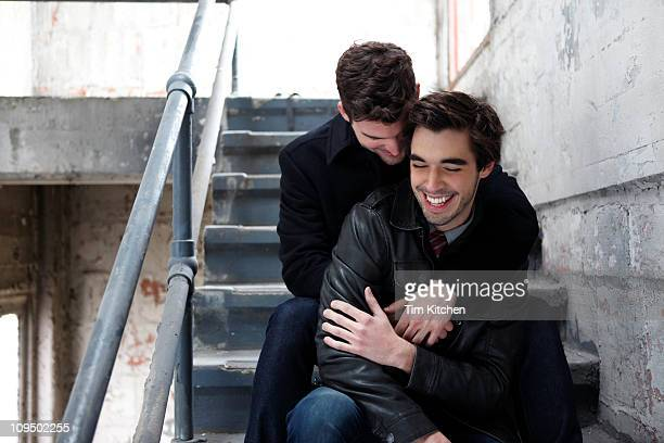 Two men cuddling on stairs, smiling