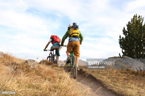 two men cycle along ridge on trail - cross country cycling stock photos and pictures