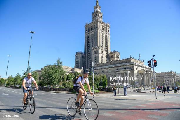 Two men cycle next to the Palace of Culture