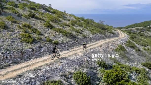 Two men cycling along ridge on trail