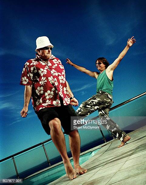 Two men dancing beside pool