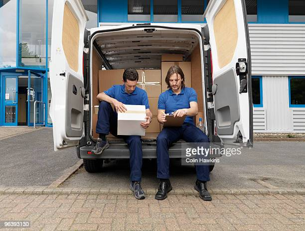 two men delivering boxes in van