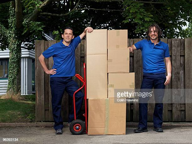 two men delivering boxes on trolley