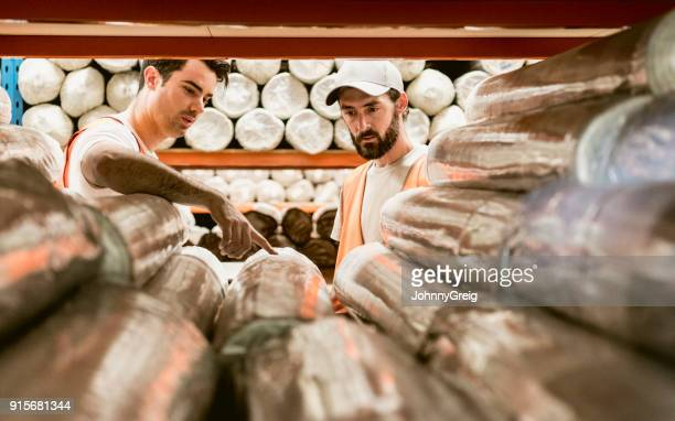 two men discussing carpets in warehouse storage facility - camera point of view stock photos and pictures
