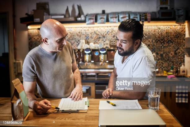 two men discussing in a coffee roastery - document stock pictures, royalty-free photos & images