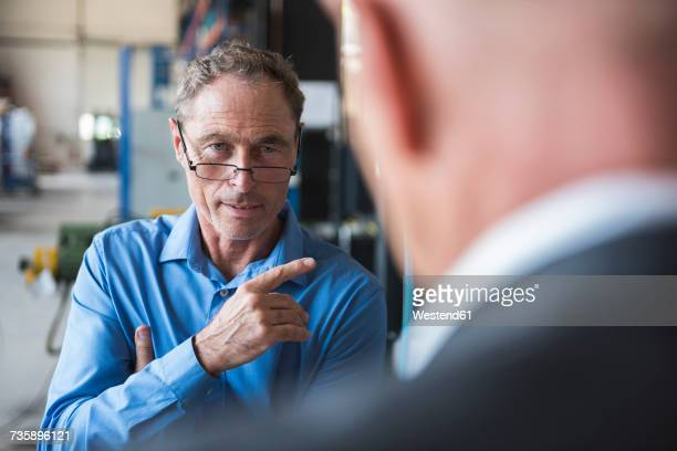 Two men discussing on factory shop floor