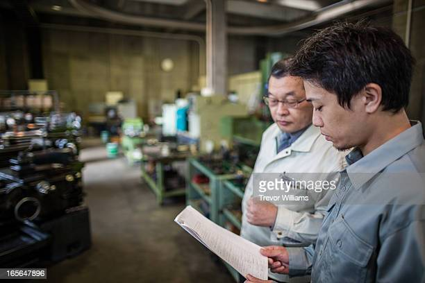 two men discussing plans in an industrial setting