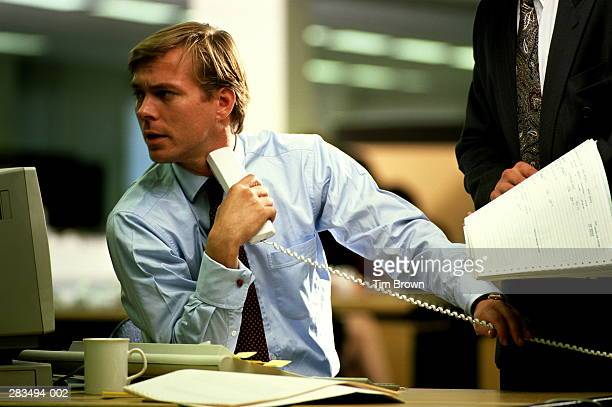 Two men discussing printout,one at desk holding phone