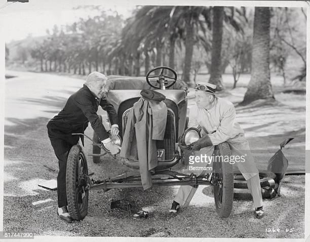 Two men dismantle a car in a scene from the 1930s comedy Love Among the Millionaires