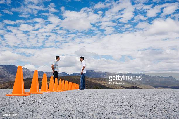 Two men divided by a row of safety cones
