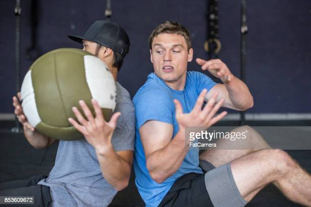 two men doing abdominal exercise with ball - passing sport stock pictures, royalty-free photos & images