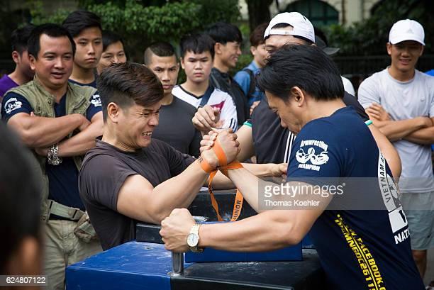 Two men doing arm wrestling surrounded by spectators on a street in Hanoi on October 30 2016 in Hanoi Vietnam