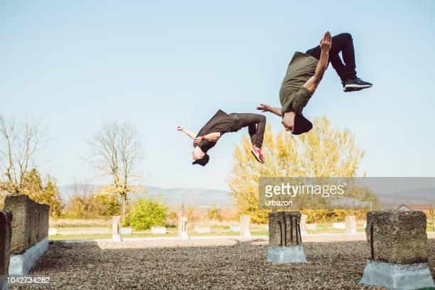 zwei männer, die frei laufenden parkour - le parkour stock-fotos und bilder