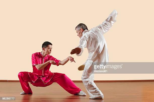 Two men doing praying mantis kick