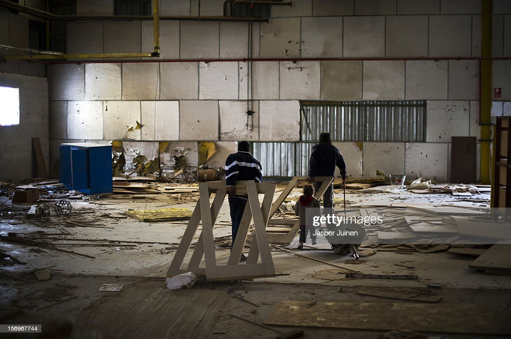 Two men drag unfinshed doors behind them, to be used as burning wood for their stoves at home, inside the abandoned Mavisa door factory on November 22, 2012 in Villacanas, Spain. During the boom years, where in its peak Spain built some 800,000 houses a year accompanied by the manufacturing of millions of wooden doors where needed, the people of Villacanas were part of Spain's middle class enjoying high wages and permanent jobs. During the construction boom years the majority of the doors used within these new developments were made in this small industrial town. Approximately seven million doors a year were once assembled here and the factory employed a workforce of almost 5700 people, but the town is now left almost desolate with the Villacanas industrial park now empty and redundant. With Spain in the grip of recession and the housing bubble burst, Villacanas is typical of many former buoyant industrial Spanish towns now struggling with huge unemployment problems.