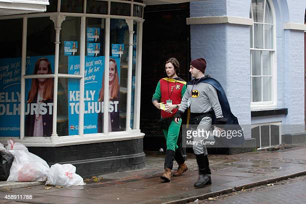 Two men dressed as Batman and Robin walk past Conservative party posters for candidate Kelly Tolhurst as they distribute leaflets for her campaign on...