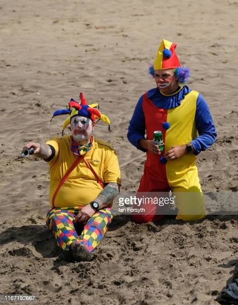 Two men dressed as clowns sit on the beach during the annual Whitby Regatta on August 10 2019 in Whitby England At over 170 years old the Whitby...