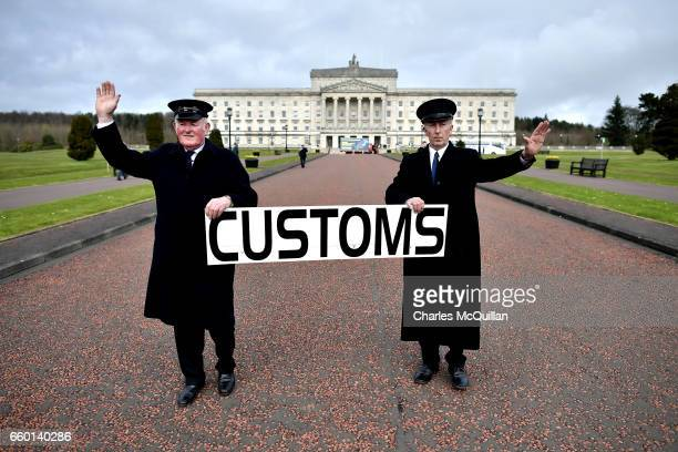 Two men dressed as customs officers take part in a protest outside Stormont against Brexit and it's possible effect on the north and south Irish...
