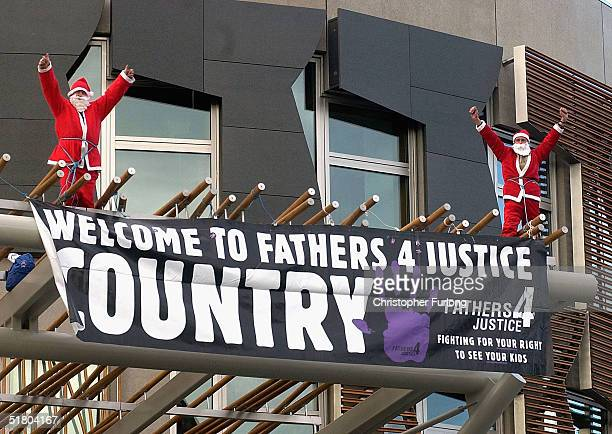 Two men dressed as Santas scale the new Scottish Parliament building Holyrood on November 30 2004 in Edinburgh Scotland The two men performed the...