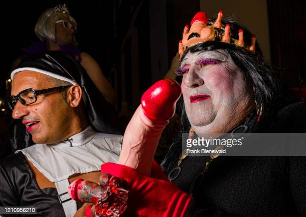 Two men, dressed up in mourning clothes and carrying a dildo, partying in the streets during the funeral procession Burial of the Sardine, the...